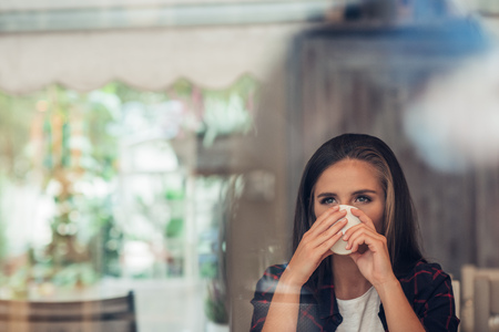looking through window: Young woman deep in thought drinking a coffee Stock Photo