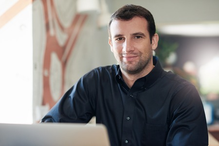 smiling businessman: Successful businessman smiling and using a laptop in an office Stock Photo