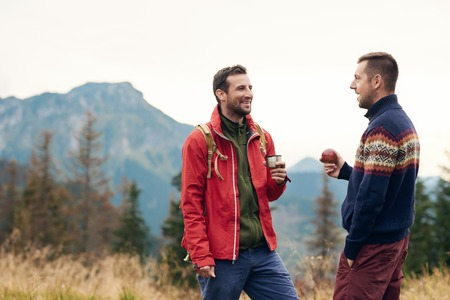 Two men taking a break while trekking in the wilderness Stock Photo