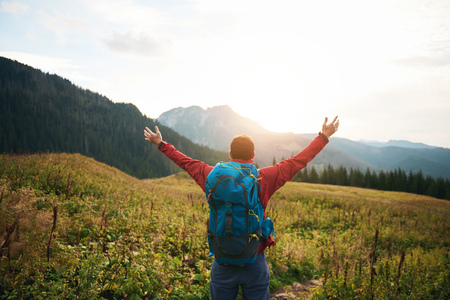 Hiker with arms raised to the sky at sunrise Stock Photo