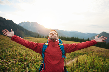 Hiker with arms raised embracing a new day Stock Photo