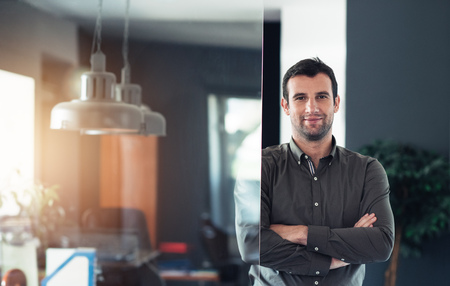 Confident businessman standing in his office