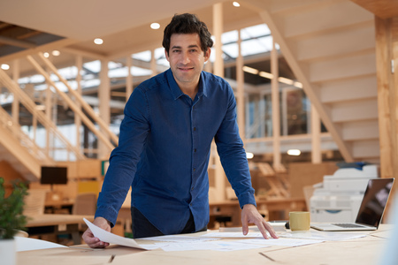 leaning: Positive young businessman sorting documents at an office desk