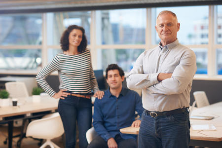 Mature manager standing in an office with colleagues behind him