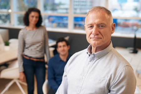 Confident manager standing in an office with staff behind him