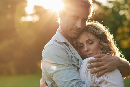 devoted: Devoted young couple hugging under the setting sun Stock Photo