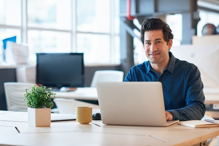 Smiling young businessman working on a laptop in an office