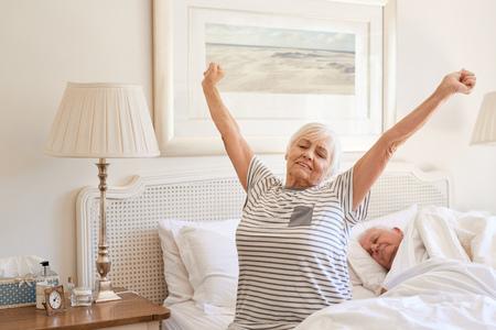 Senior mujer despertando con un estiramiento en la mañana Foto de archivo - 74828683