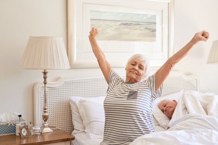 Senior woman waking up with a stretch in the morning Stock Photo