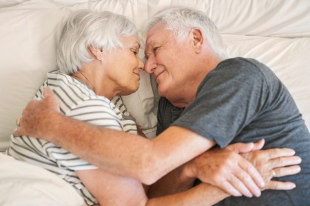 warmly: Happy senior couple smiling warmly at each other in bed Stock Photo