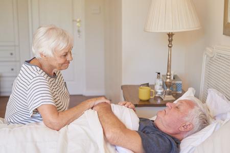 年配の女性がベッドで彼女の病気の夫の世話