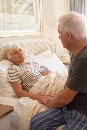 Senior man consoling of his sick wife in bed Stock Photo