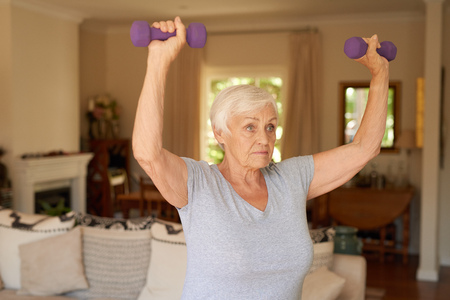 Fit and active senior woman lifting dumbells at home