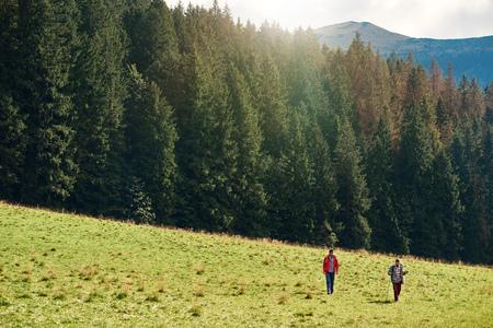 Hikers walking in a field near forest