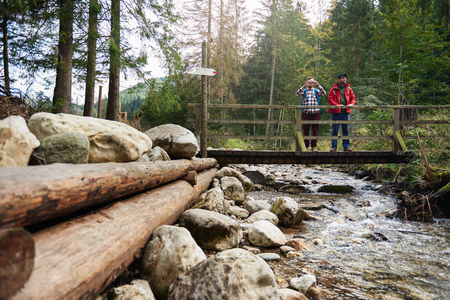 bridge in nature: Hikers photographing nature from a river bridge
