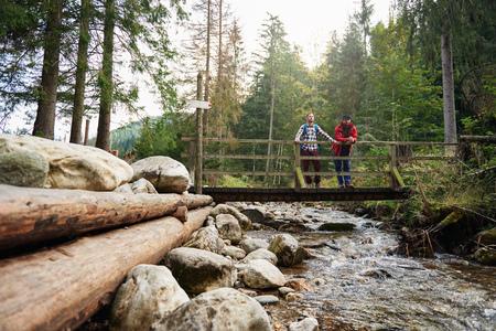 bridge in nature: Hikers admiring nature from a river bridge Stock Photo