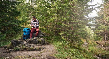 Hiker sitting on a rock using cellphone gps