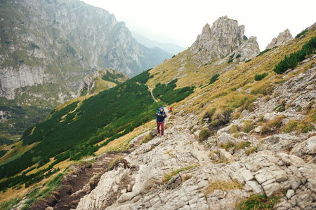 Hikers walking along a trail in rugged mountain terrain Stock Photo
