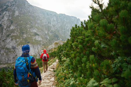 Two men hiking along a rocky trail in the mountains