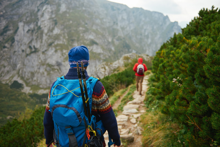 Hikers makng their way along a trail in the mountains Stock Photo