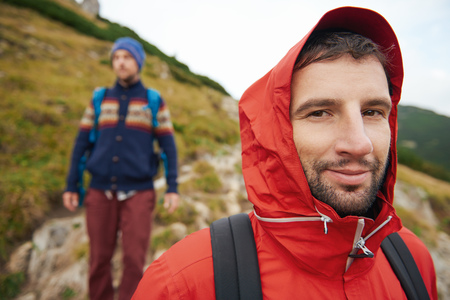 Hooded hiker on the trail with a friend behind him