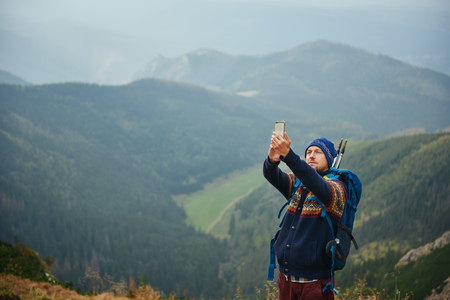Young hiker taking a selfie from a mountain peak