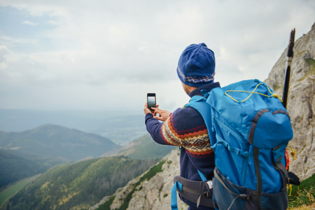 Hiker photographing the view from high atop a mountain Stock Photo