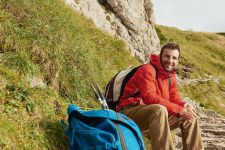 one man: Smiling hiker sitting on a trail in the mountains