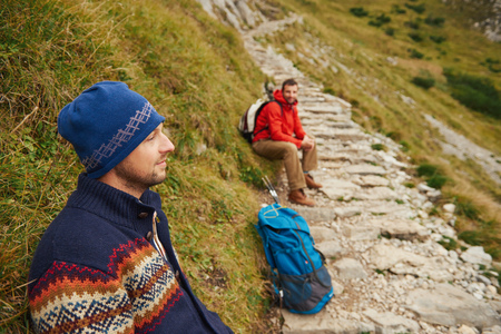 Two hikers resting on a rugged mountain trail