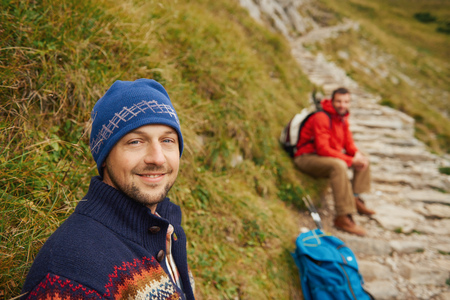 Smiling hikers resting on a rugged mountain trail