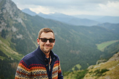one young man: Smiling hiker standing in front of a majestic mountain landscape