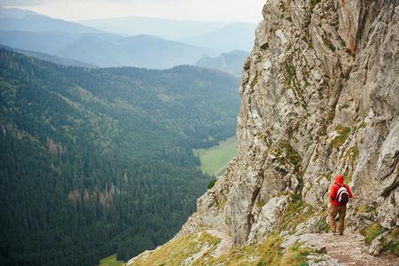 Lone hiker walking down a rugged mountain trail