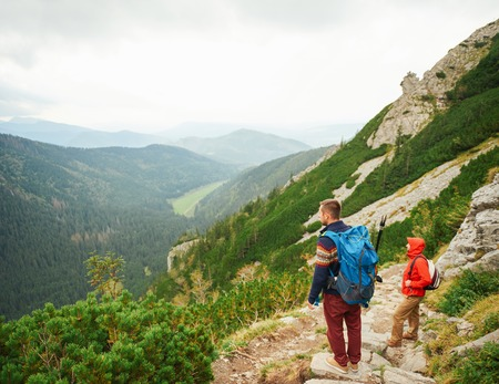 Hikers taking in the view from a rugged mountain trail Stock Photo