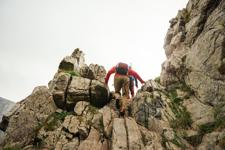 Two hikers scrambling up a rocky mountain trail