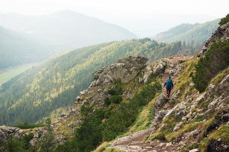 Hiker trekking aone along a rock mountain path