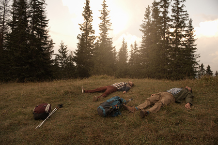Tired hikers lying on grass after a trek