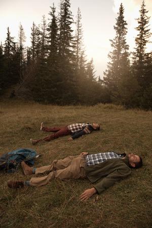 Hikers lying on the grass after a long wilderness trek