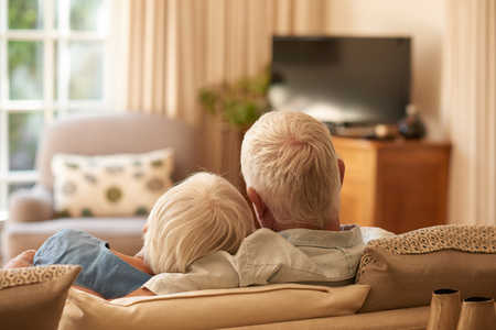 Rearview of an affectionate senior couple relaxing in each others arms on a couch in their living room at home Stock Photo
