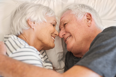 warmly: Devoted senior couple smiling warmly at each other in bed