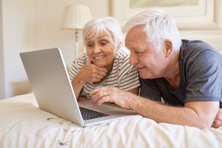 mujer en la cama: Happy senior couple using a laptop together in bed