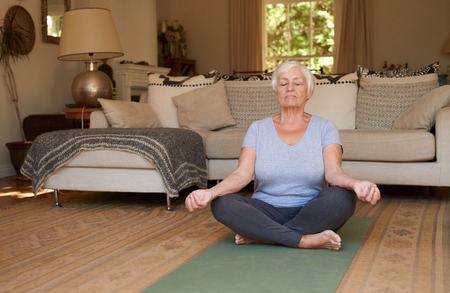 Senior woman sitting in the lotus position meditating at home