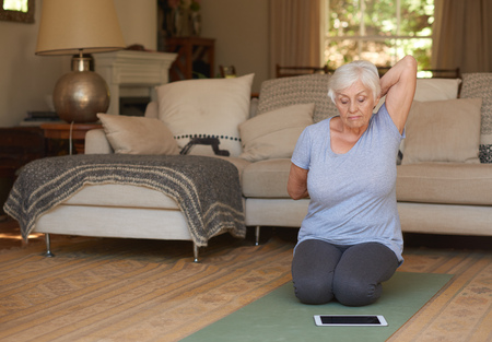 Senior woman practising yoga at home with a digital tablet
