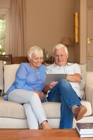 couple on couch: Happy seniors browsing the internet from their living room sofa Stock Photo