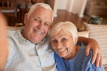 couple on couch: Happy senior couple taking selfies together on their sofa Stock Photo