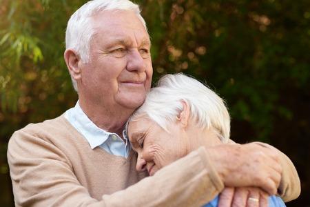 warmly: Romantic senior man warmly hugging his woman outside