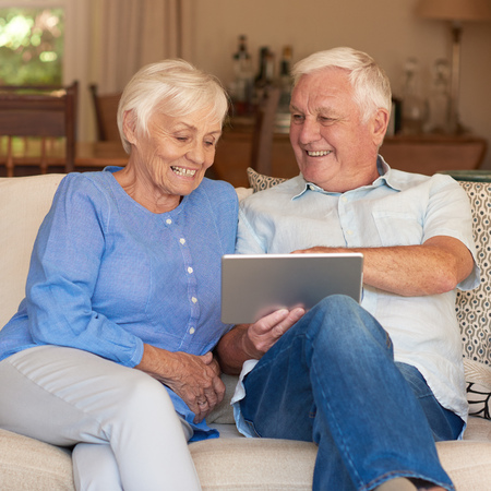 couple on couch: Content seniors using a touchscreen tablet on their couch Stock Photo