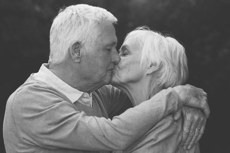 warmly: Cute senior couple warmly kissing outdoors