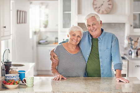 Smiling senior couple content at home in their kitchen