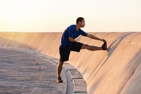 Atletische jonge Aziatische man strekt zijn benen voor een rit