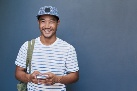 Smiling young Asian man using a cellphone outside